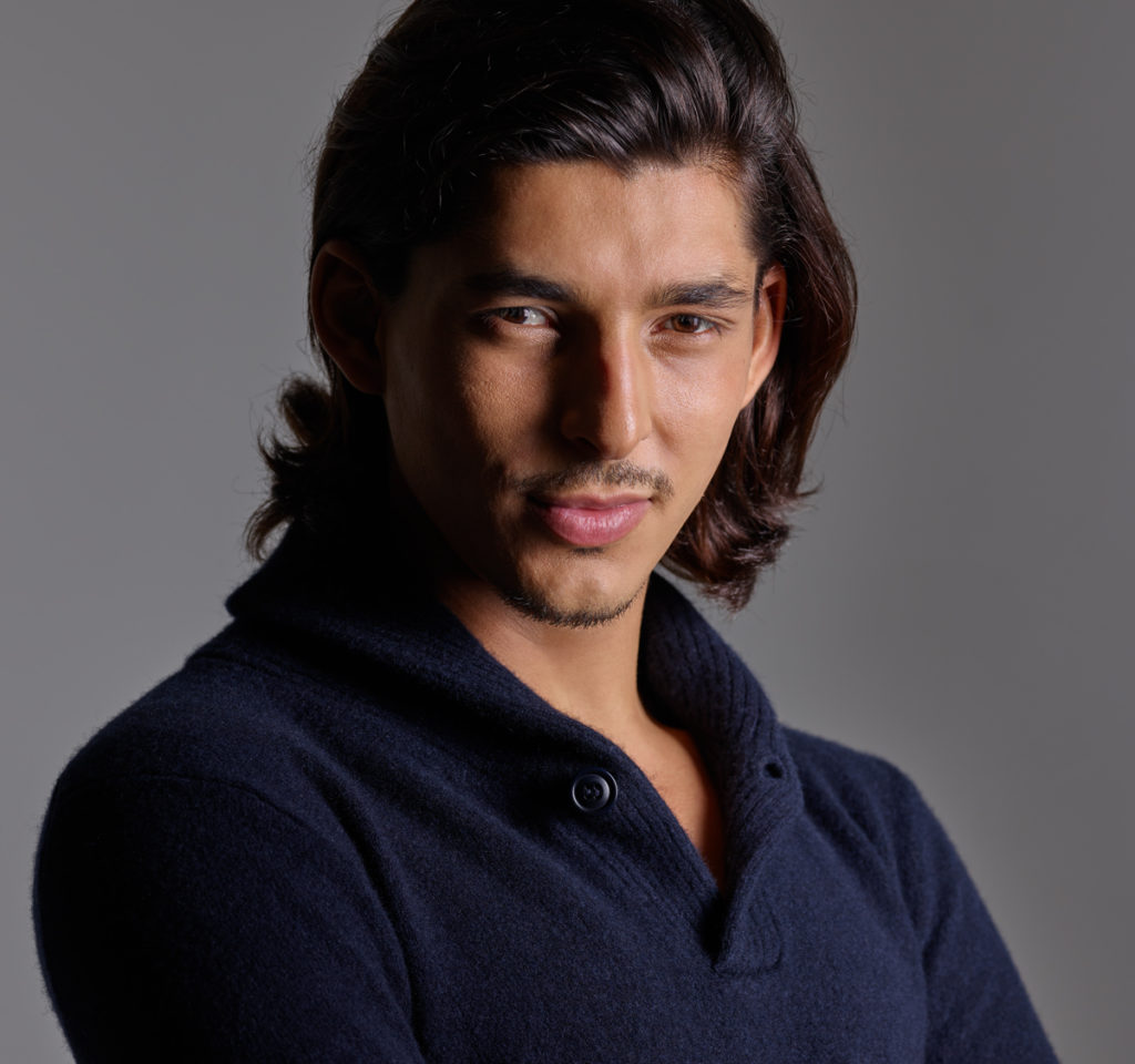 Professional headshot of a male artist with dark long hair wearing a blue sweater taken at NYC Headshot.